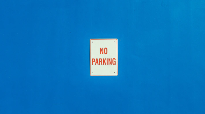No parking sign on blue wall